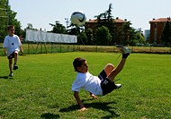 Young soccer player doing an overhead kick