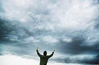 Man with Arms Raised with Cloudy Sky in Background