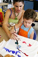 Children´s Museum, tee shirt decorating workshop, Hispanic boy, mother, painting. Miami. Florida. USA.