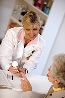 Pharmacist assisting elderly woman with her prescription.
