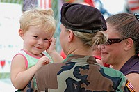 Female soldier at site of memorial of 14 dead Marines in Brook Park Ohio, some with baby, about to go to Iraq. USA.