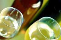 Close-up of two glasses of wine with a wine bottle