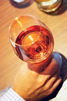 High angle view of a person's hand holding a glass of wine