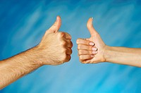 Close-up of a man and a woman's hands making a thumbs up sign