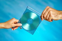 Close-up of a man and a woman's hands holding a compact disk