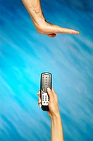 Woman's hand holding a remote control with a man's hand making stop gesture