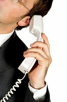 Close-up of a businessman holding a telephone receiver up to his ear