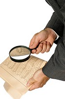 Close-up of a businessman holding a magnifying glass over a newspaper