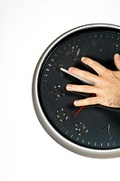 Close-up of a person's hand holding a clock