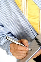 Mid section view of a businessman writing in a notebook