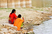 Two women sitting on the banks of a river, Gadi Sagar, Jaisalmer, Rajasthan, India