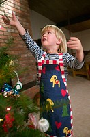 3 year old girl decorating Christmas tree
