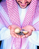 Arab businessman holding golden eggshells and money