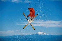 Skier jumping in mid-air, with skis crossed