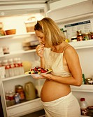 Pregnant Woman Eating Fruit in Front of Fridge