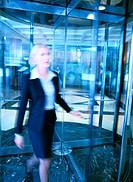 Businesswoman Walking Through a Revolving Door
