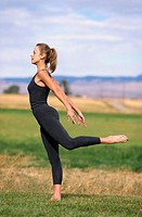 Woman Doing Yoga in a Field