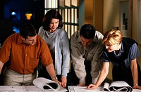 Group of Architects Reviewing Blueprints Together