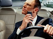 Businessman Shaving While Driving to Work
