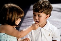 High angle view of a girl feeding nuts to her brother