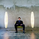 Man sitting on chair in between 2 lamps