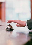 Man ringing bell for service at hotel´s front desk, close-up of hand