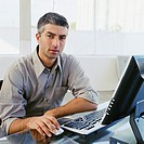 Businessman seated at desk in front of computer, portrait