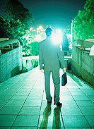 Businessman walking down concrete path, rear view, night