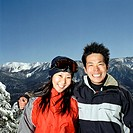 Young couple standing on snowy slope, portrait