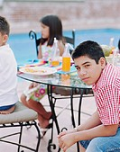 Three children eating at table on patio, focus on boy (12-14)