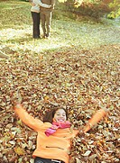 Girl (12-14) lying in pile of leaves, parents embracing in background