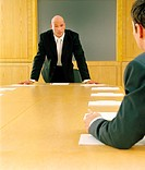 Two businessmen in boardroom, focus on man standing at head of table