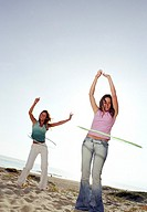 Two women playing with plastic hoops on beach