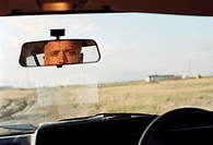 Man in car looking in rear view mirror