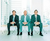 Three businessmen sitting on chairs in lobby, looking up