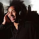 Man wearing headphones, laughing outdoors
