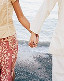 Couple holding hands on beach, close up