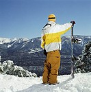 Young man standing with snowboard on snowy slope, rear view