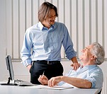 Businessman standing with hand on seated man´s shoulder in office