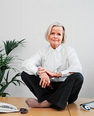 Senior businesswoman sitting cross-legged on desk, portrait