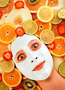Teenage girl (15-17) wearing face mask, surrounded by sliced fruit