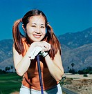 Woman leaning on golf club, resting chin on hands, portrait