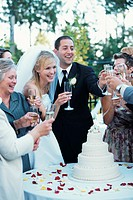 Bride, groom and guests raising toast with champagne at reception