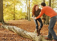 Couple balancing hand in hand on tree trunk, smiling