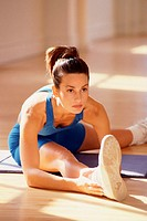 Woman doing floor stretches, sitting on exercise mat