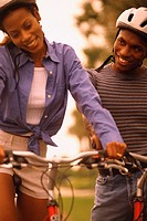 Woman and man riding bicycles, both wearing helmets and smiling