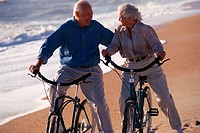 Man and woman riding bicycles along beach