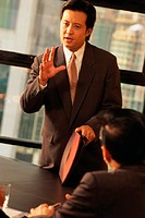 Man standing, speaking to people in boardroom