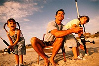 Father teaching daughter and son how to fish from shore
