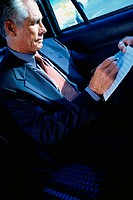 Businessman in cab working on report
